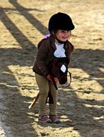 Little girl riding stick horse at walk trot